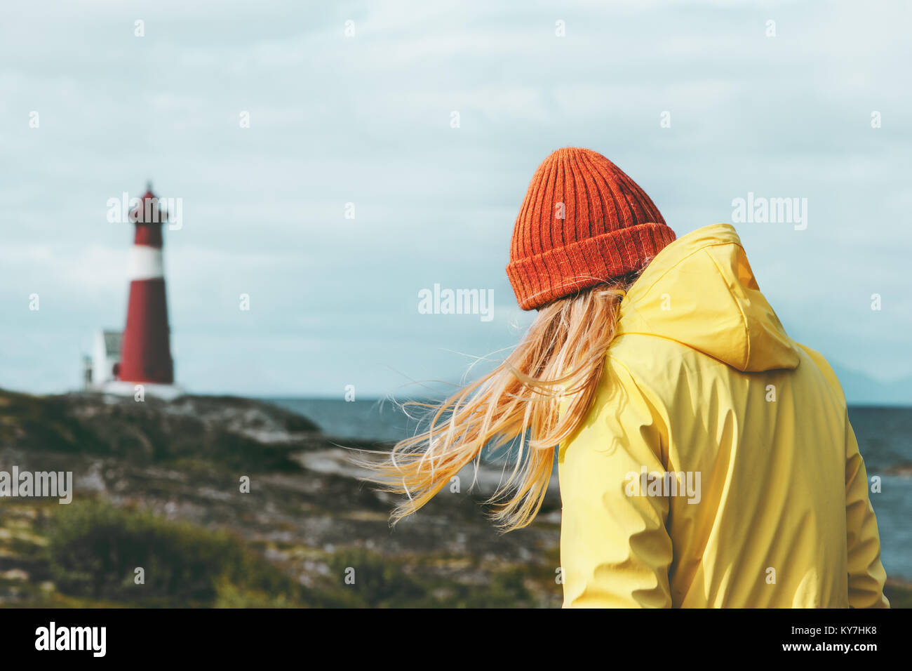 Traveler girl walking at Norway lighthouse sea landscape Travel Lifestyle concept adventure scandinavian vacations - Stock Image