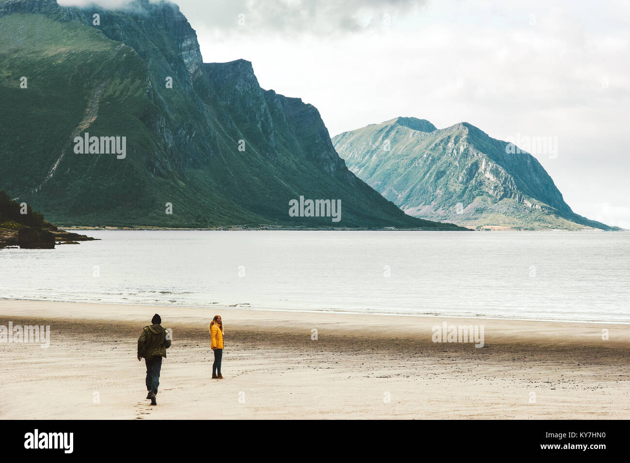 Couple in love Man running to Woman at sea Norway beach Travel happy emotions Lifestyle concept romantic vacations - Stock Image