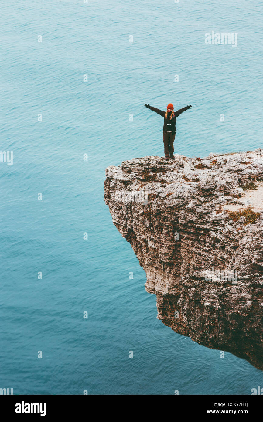 Happy traveler on cliff above sea hands raised Travel Lifestyle success motivation concept adventure active vacations - Stock Image