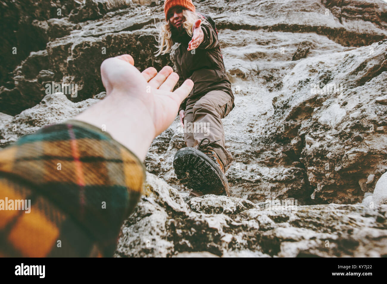 Couple Man and Woman help giving hands climbing rocky mountains Love and Travel Lifestyle concept hiking adventure - Stock Image