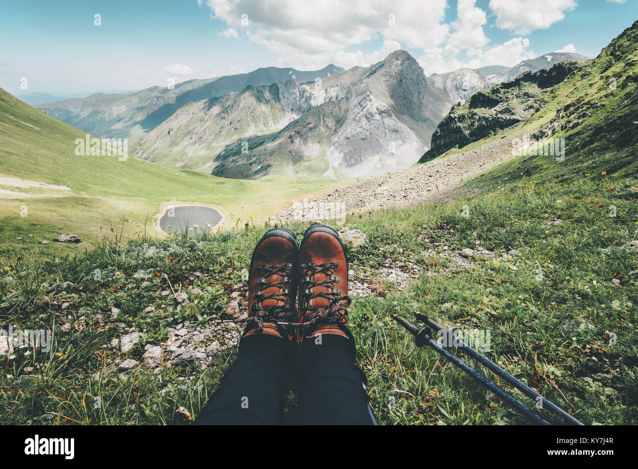 Feet trekking boots and mountains landscape on background Travel Lifestyle adventure vacations concept - Stock Image