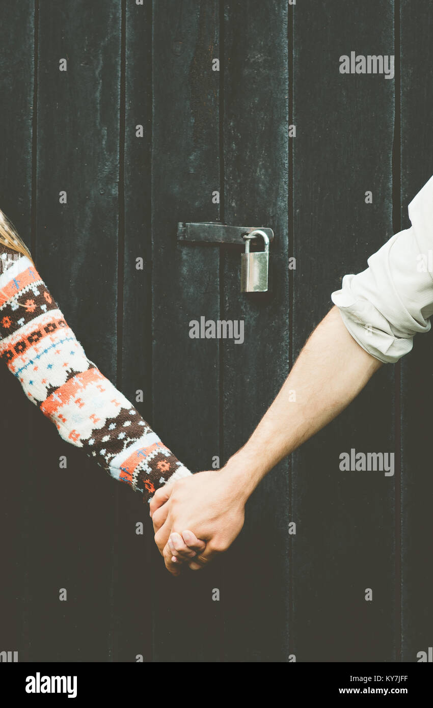 Love Couple hands holding forever together Lifestyle wooden background and lock over people taboo concept - Stock Image