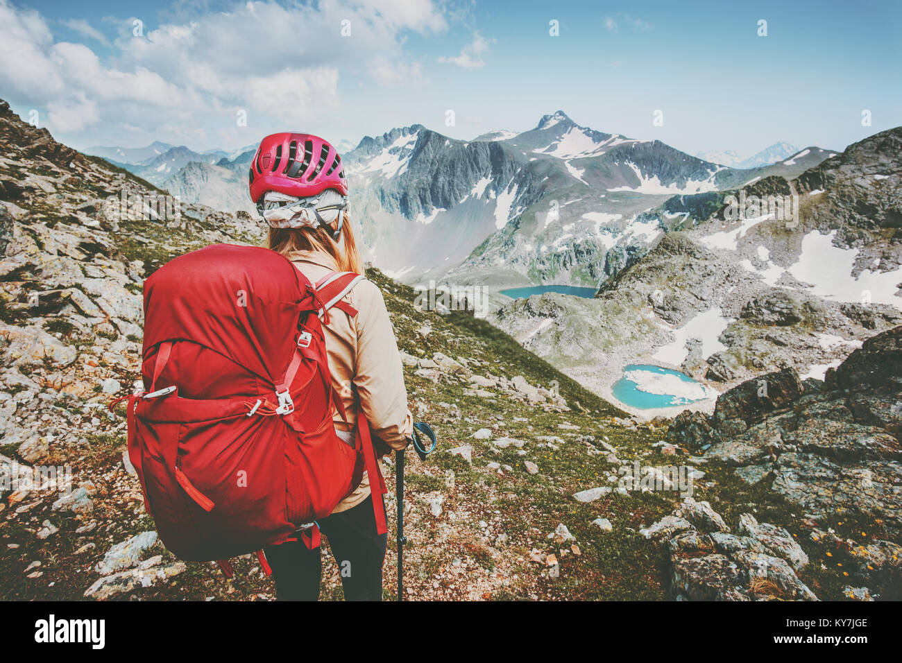 Adventurer tourist hiking in mountains with backpack Travel Lifestyle hiking adventure concept summer vacations - Stock Image