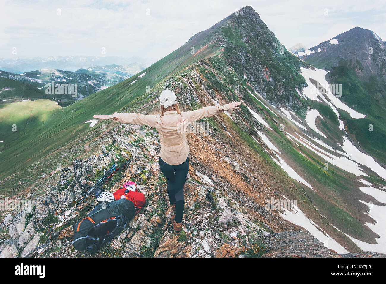 Hiker woman happy hands raised on mountain summit Travel Lifestyle adventure concept summer vacations outdoor exploring - Stock Image