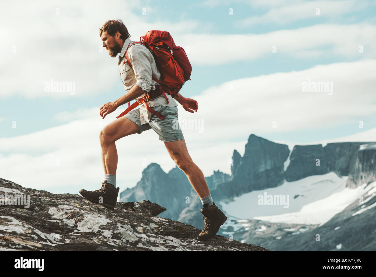 Man trail running in mountains with backpack Norway Travel hiking lifestyle concept active weekend summer vacations - Stock Image