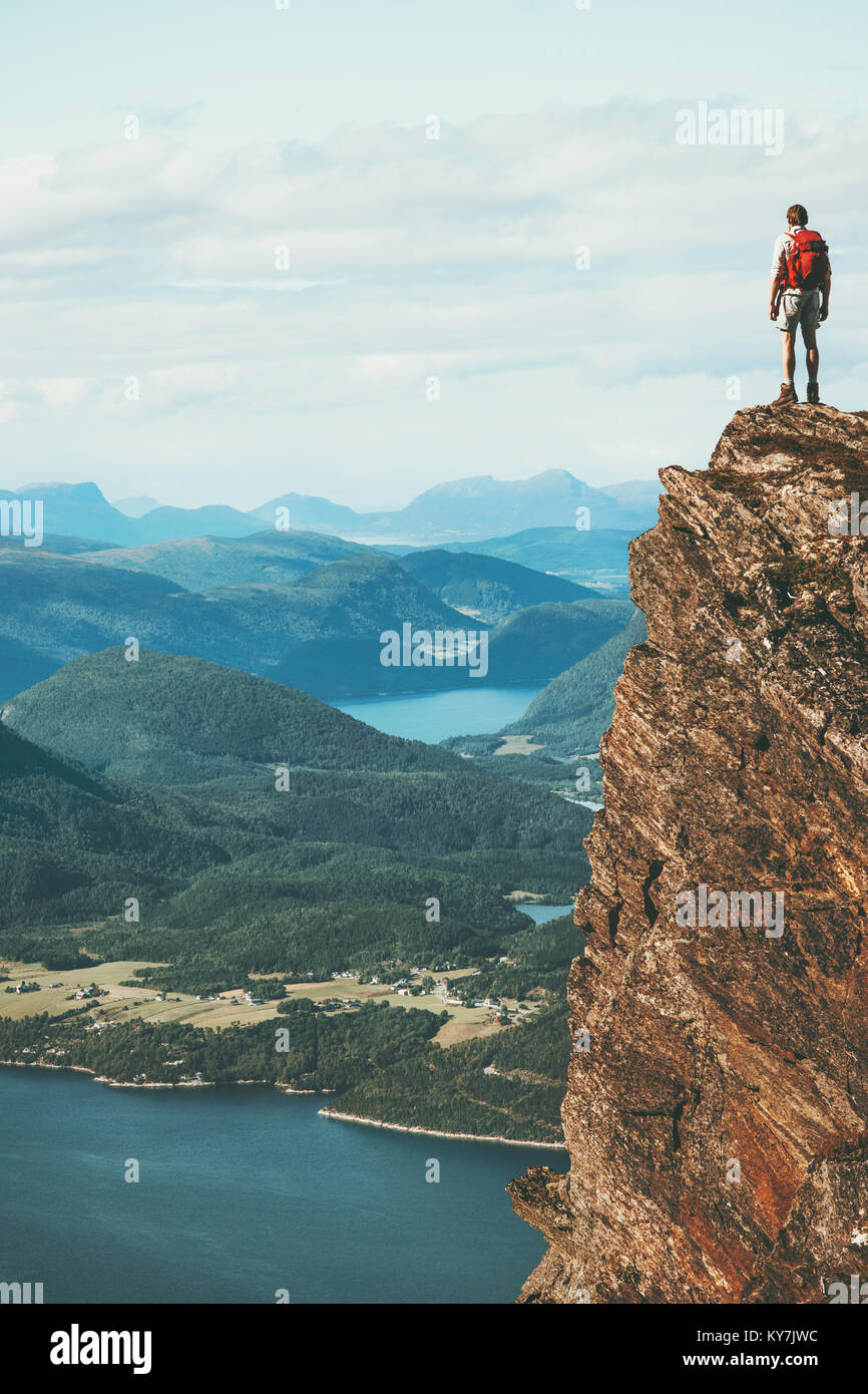 Traveler on cliff mountains over fjord enjoying Norway landscape Travel Lifestyle success motivation concept adventure - Stock Image