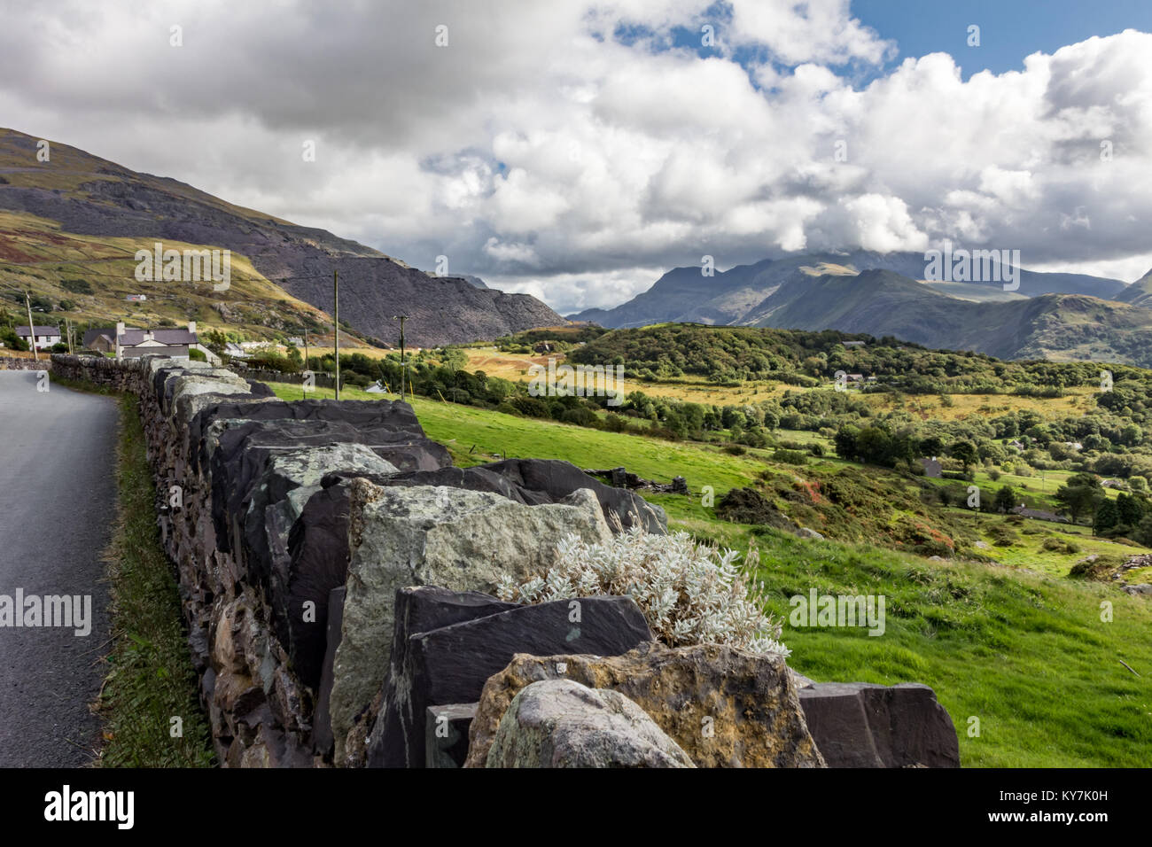 Landscape scene with dry stone wall in foreground and Mount Snowdon in background covered in clouds - Stock Image