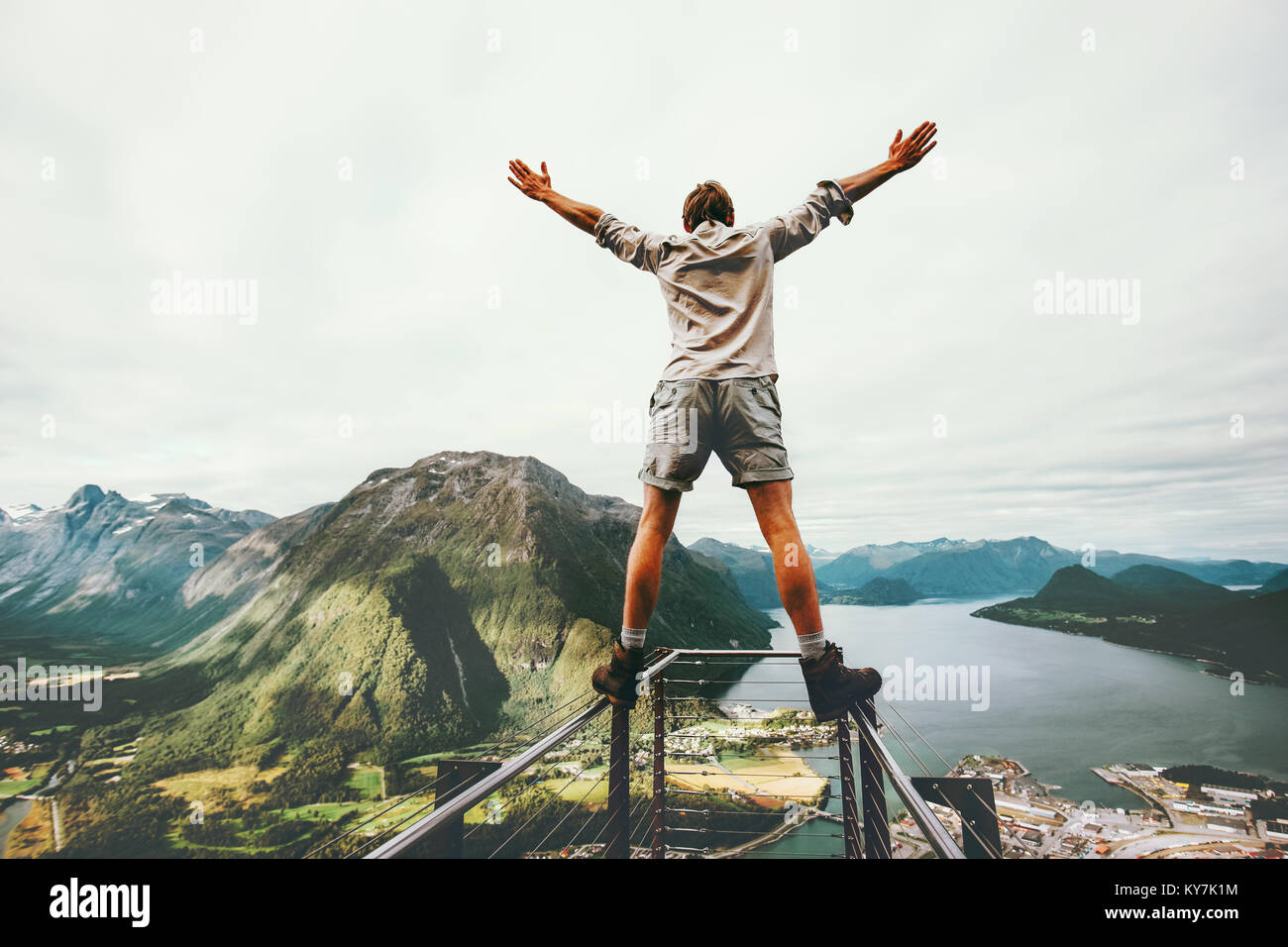 Man raised hands balancing at the edge cliff Rampestreken landmark in Norway mountains Travel lifestyle risk concept - Stock Image