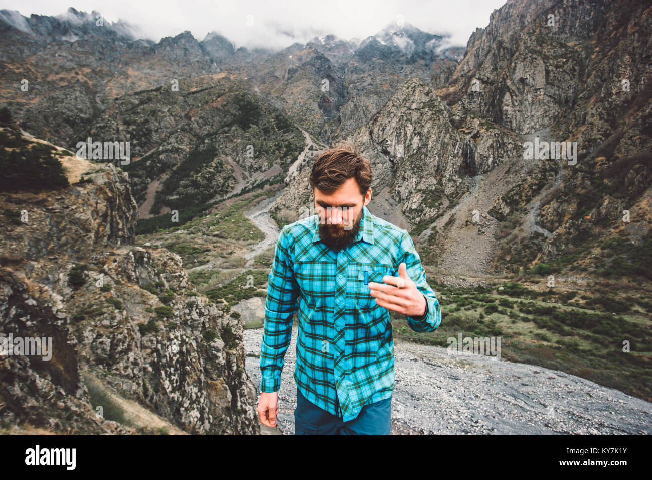 Bearded Man walking in mountains Travel Adventure lifestyle concept active weekend summer vacations - Stock Image