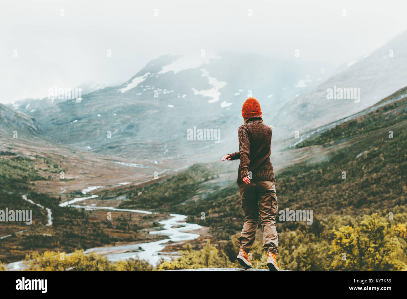 Woman walking outdoor foggy mountains on background Travel Lifestyle getaway concept adventure active vacations - Stock Image