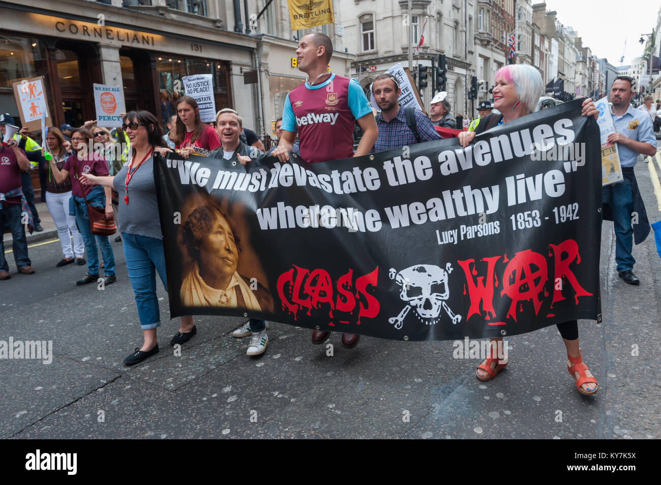 Adam Clifford levitates behind the Class War banner as they march in support of the United Voices of the World protest - Stock Image