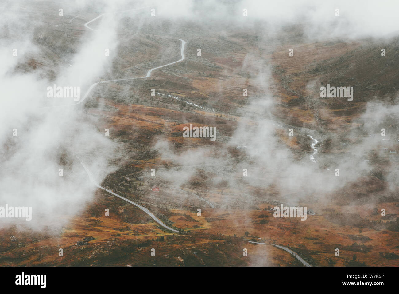 Foggy clouds tundra mountains and road Landscape in Jotunheimen national park Norway Travel scenery aerial view - Stock Image
