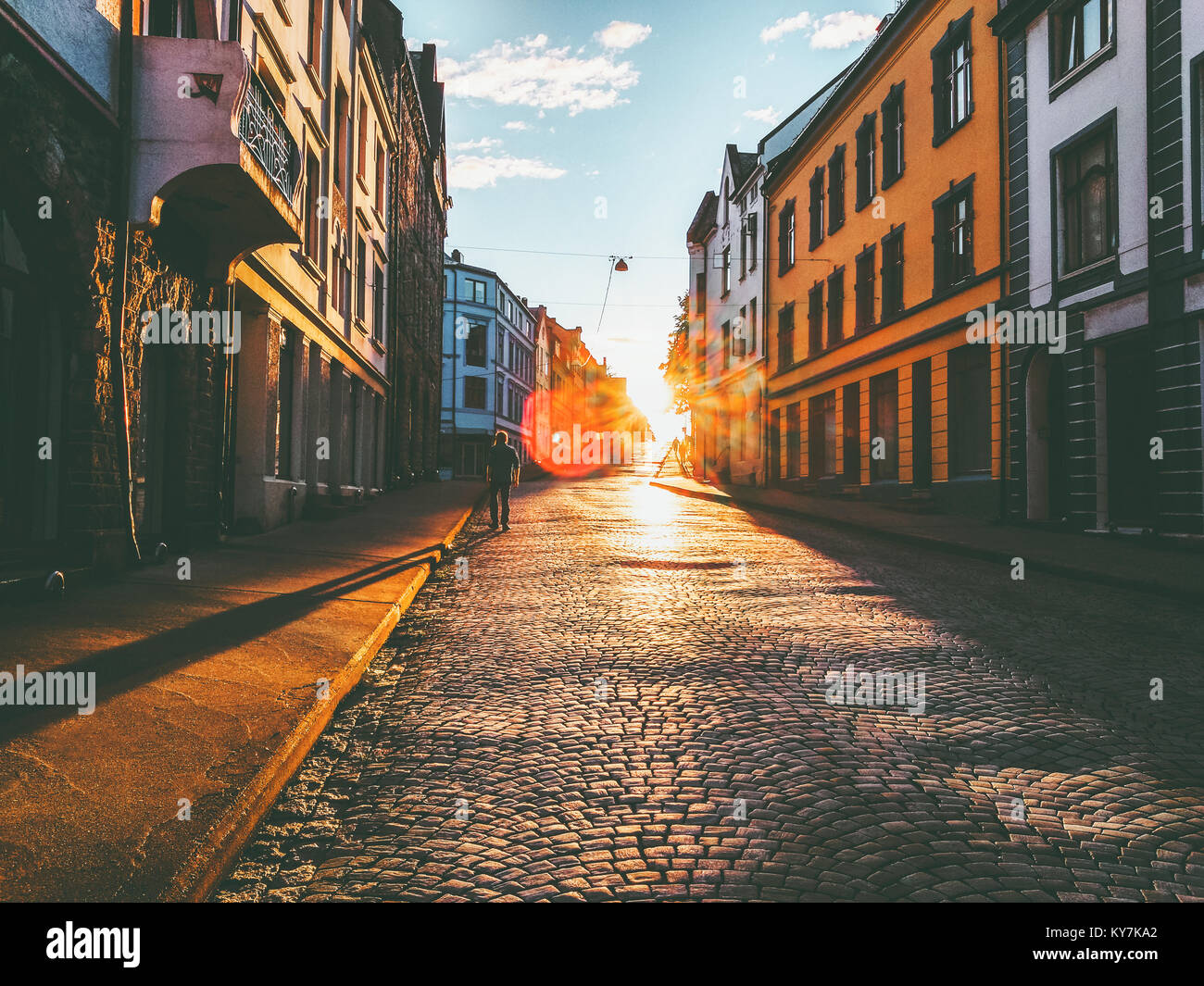 Man walking alone at sunset street Travel Lifestyle concept vacations cobblestone road city in Norway - Stock Image