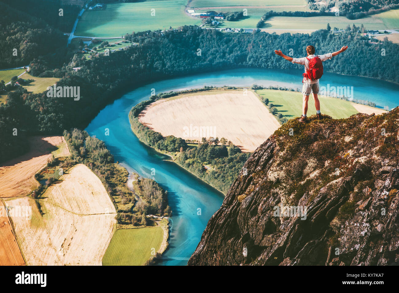 Success Man backpacker standing on cliff mountain hands raised Travel Lifestyle motivation concept adventure active - Stock Image