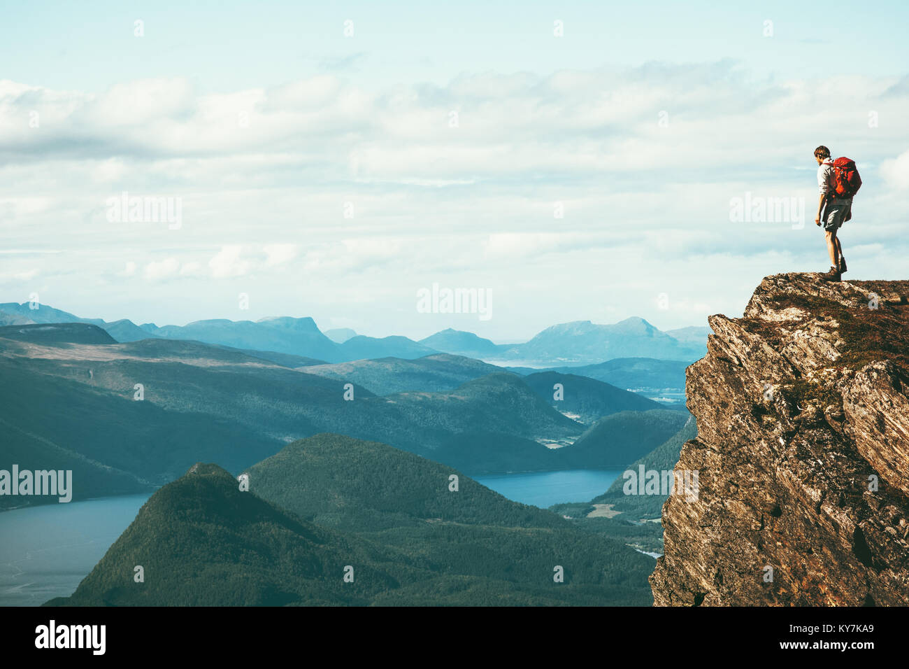 Man explorer standing on cliff alone mountain summit over fjord Norway landscape Travel Lifestyle success motivation - Stock Image