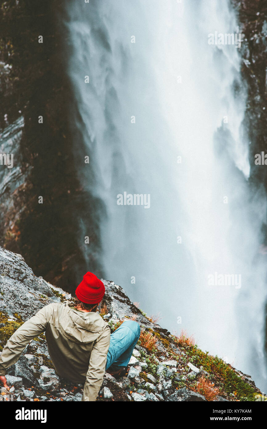 Man tourist on cliff looking at waterfall outdoor Travel Lifestyle success concept adventure vacations in mountains - Stock Image