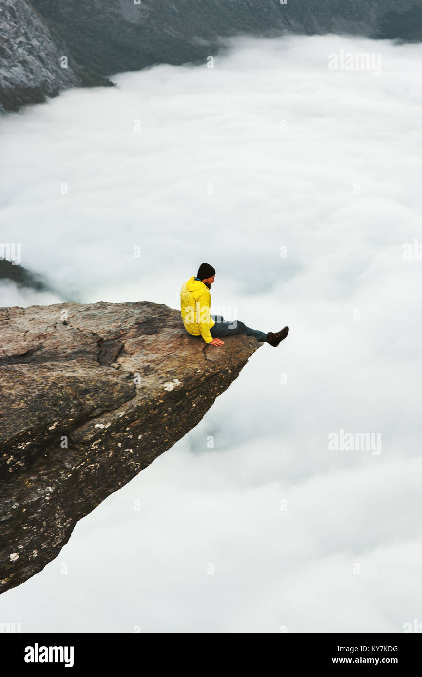 Man traveler sitting on Trolltunga rocky cliff edge in Norway mountains Travel Lifestyle adventure emotional concept - Stock Image