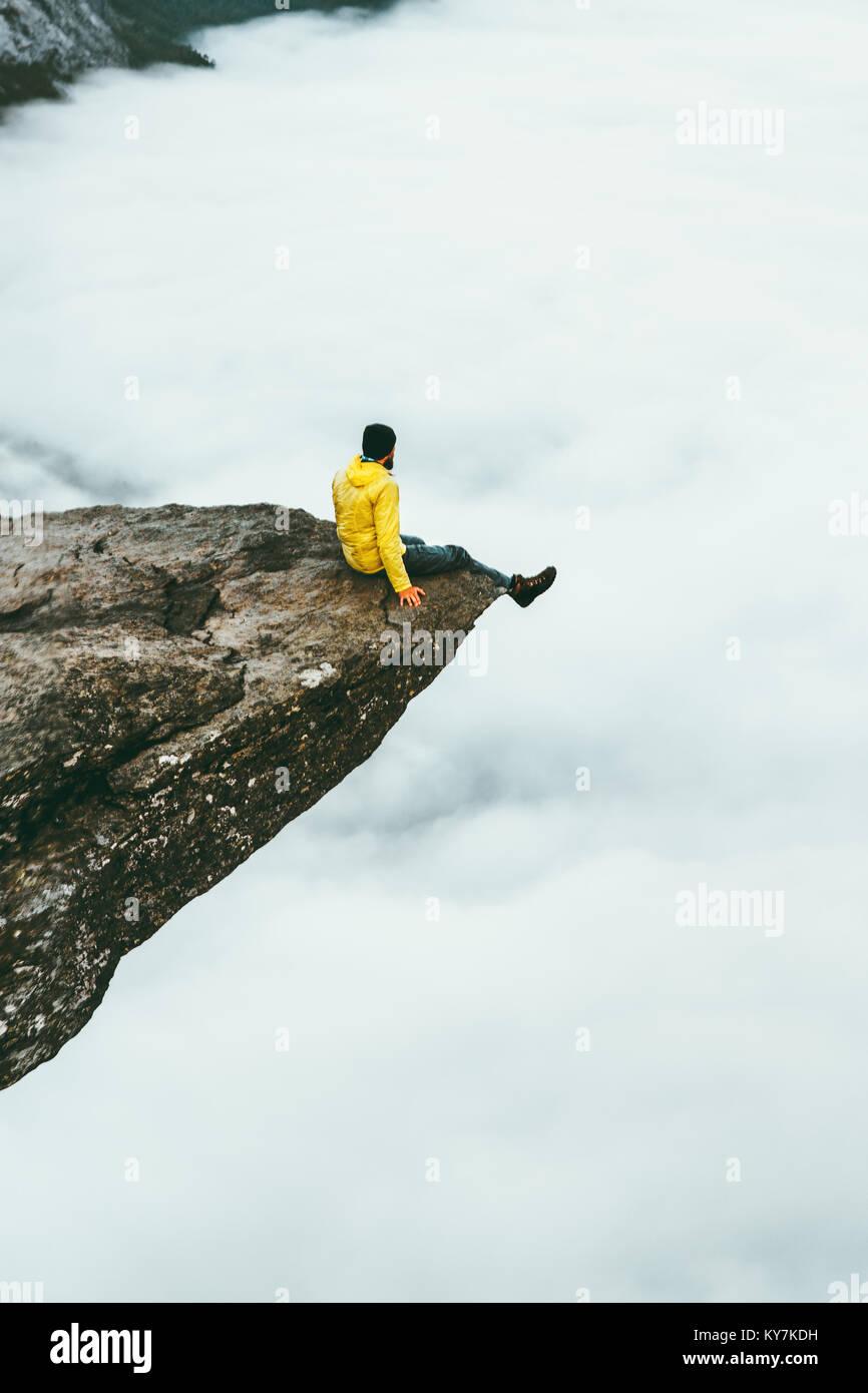 Man traveler sitting on Trolltunga rocky cliff edge in Norway mountains Travel Lifestyle adventure concept extreme - Stock Image
