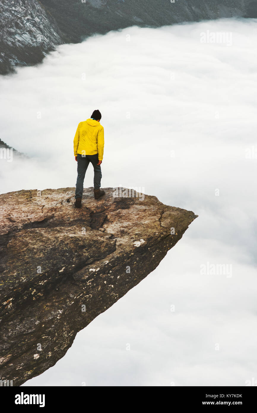 Man explorer standing on Trolltunga rocky cliff edge in Norway mountains Travel Lifestyle adventure concept extreme - Stock Image