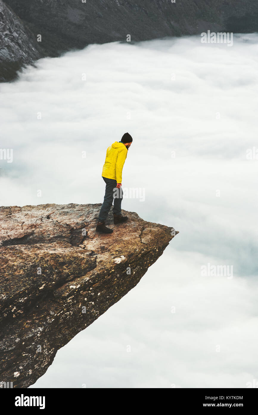 Man traveler standing on Trolltunga rocky cliff edge in Norway mountains Travel Lifestyle adventure concept extreme - Stock Image