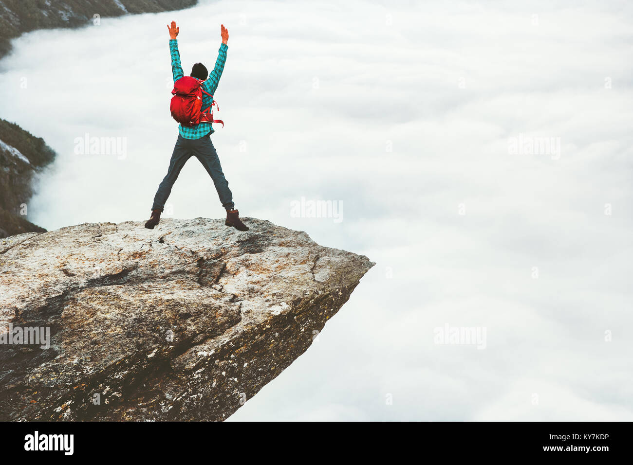 Man tourist jumping on Trolltunga rocky cliff mountains Travel Lifestyle wanderlust adventure concept active summer - Stock Image