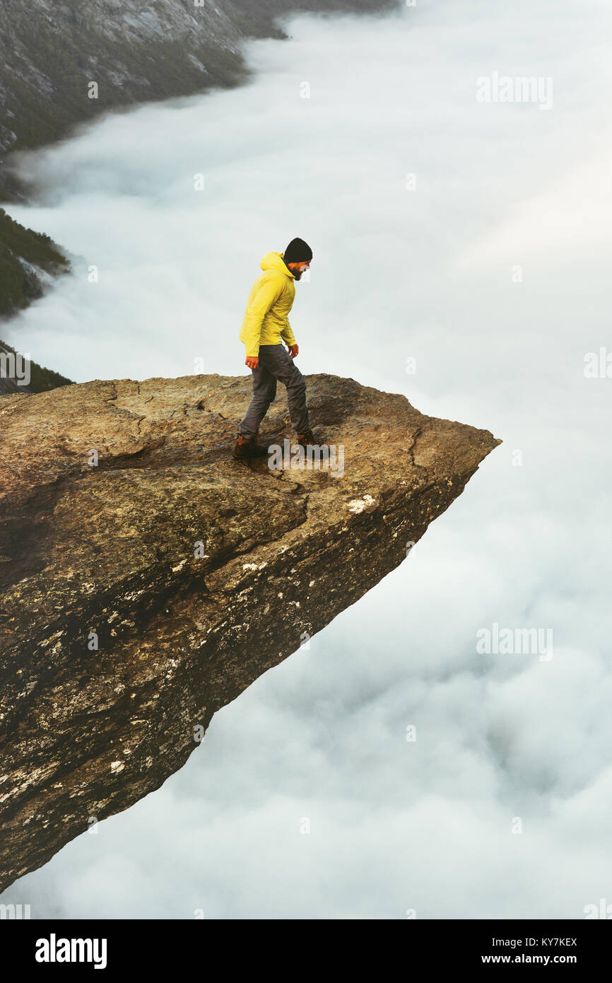 Man traveler on Trolltunga rocky cliff edge mountains Travel Lifestyle adventure emotional concept wanderlust vacations - Stock Image