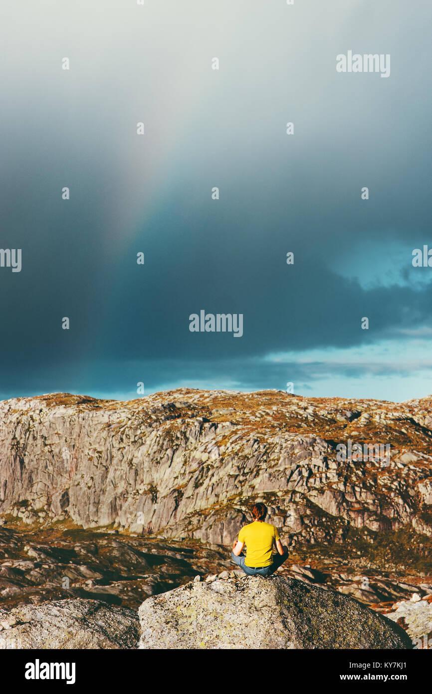 Rainbow mountains landscape and Man meditating yoga Travel Lifestyle relaxation emotional calm concept outdoor harmony - Stock Image