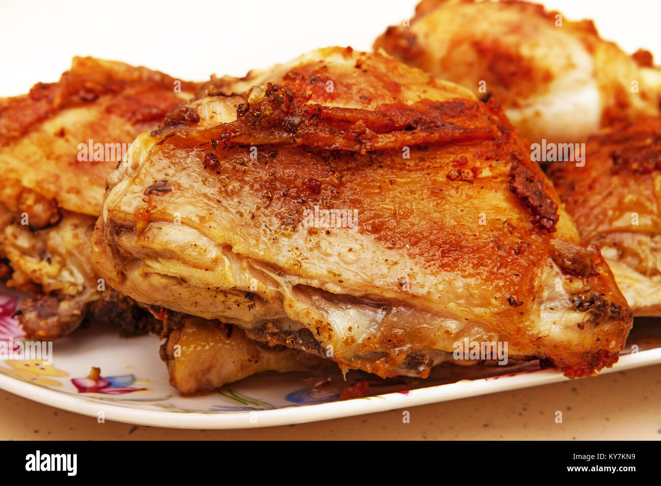 close-up of fatty fried chicken piece on plate - Stock Image