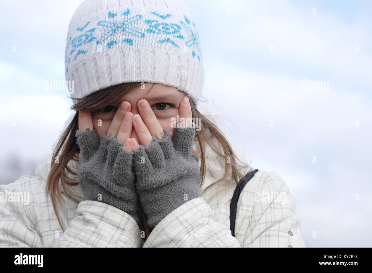 Portrait Of Nice Young Girl Looking Between Her Fingers Stock