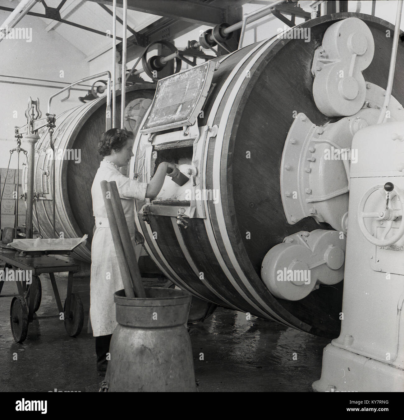1950s, historical, female dairy worker in white coat checking the butter that has been made inside a large barrel Stock Photo