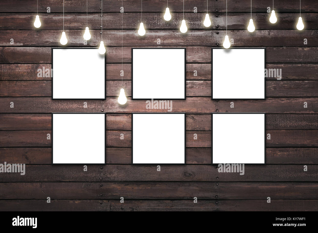 Rustic wooden plank wall with isolated white posters in black frames ...