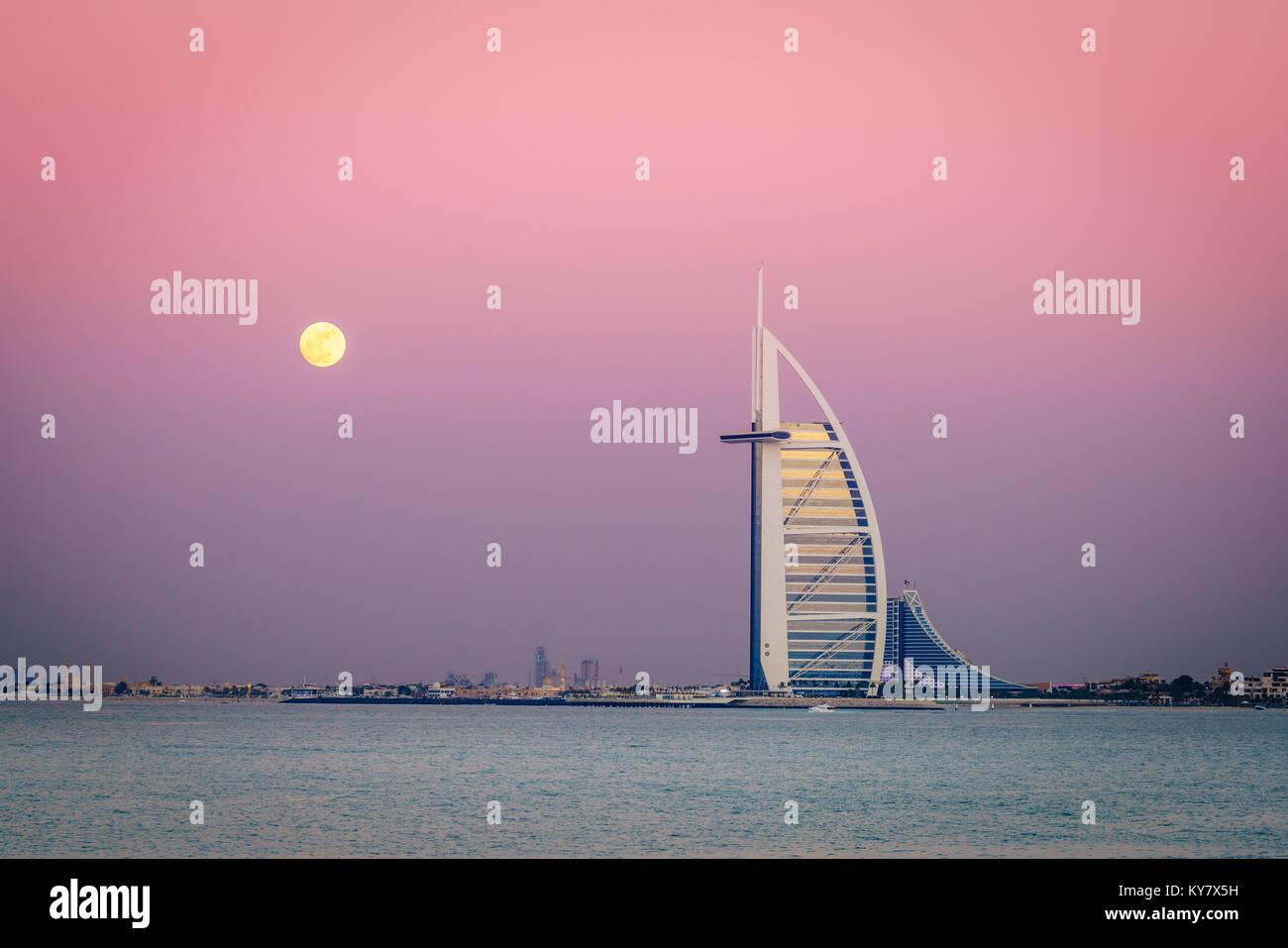 Dubai, UAE, December 13, 2016: full moon is rising over Burj Al Arab - the world's only 7-star luxury hotel Stock Photo