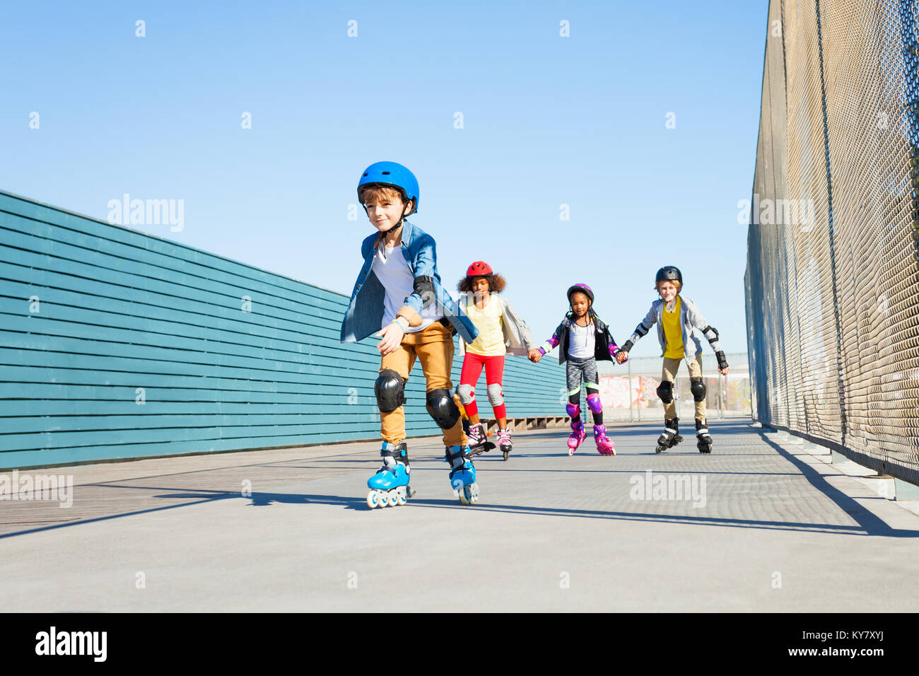 Happy preteen boy playing roller skates with friends outdoors at stadium - Stock Image