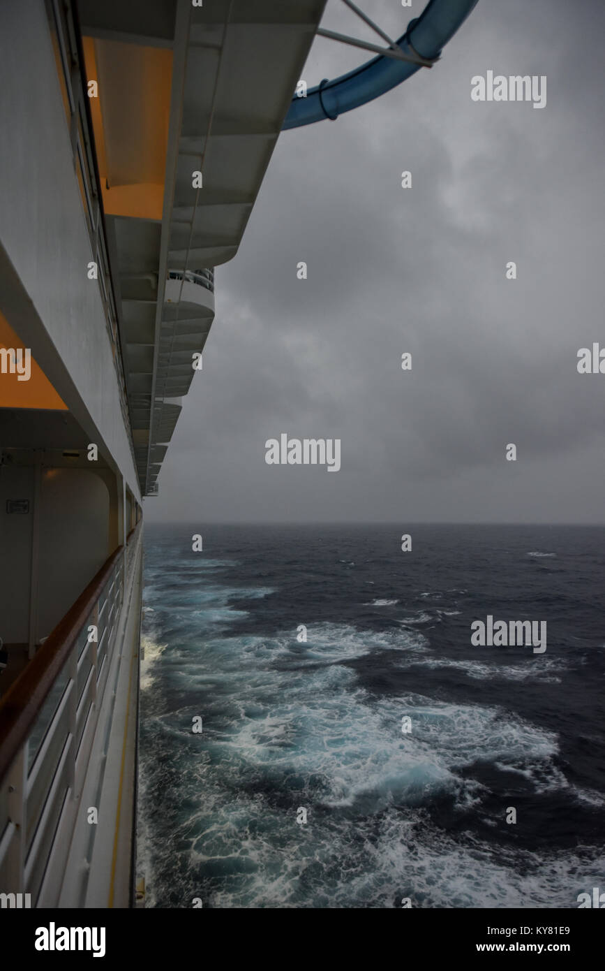 A balcony view looking behind a cruise ship as it sails under gray stormy / cloudy skies in the Atlantic Ocean heading - Stock Image