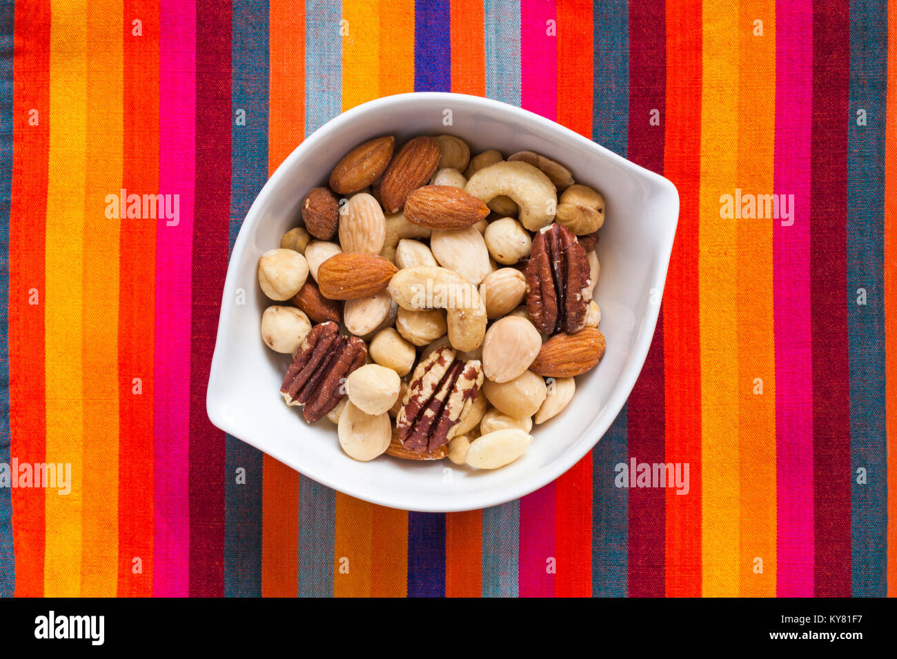 White bowl of Tesco finest roasted nut selection on colorful striped background. Mixed roasted nuts delicately seasoned - Stock Image