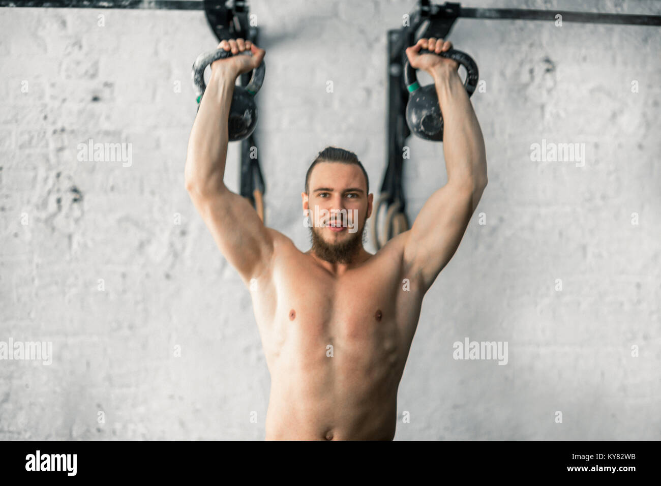 man lifting two kettlebell workout exercise at gym - Stock Image