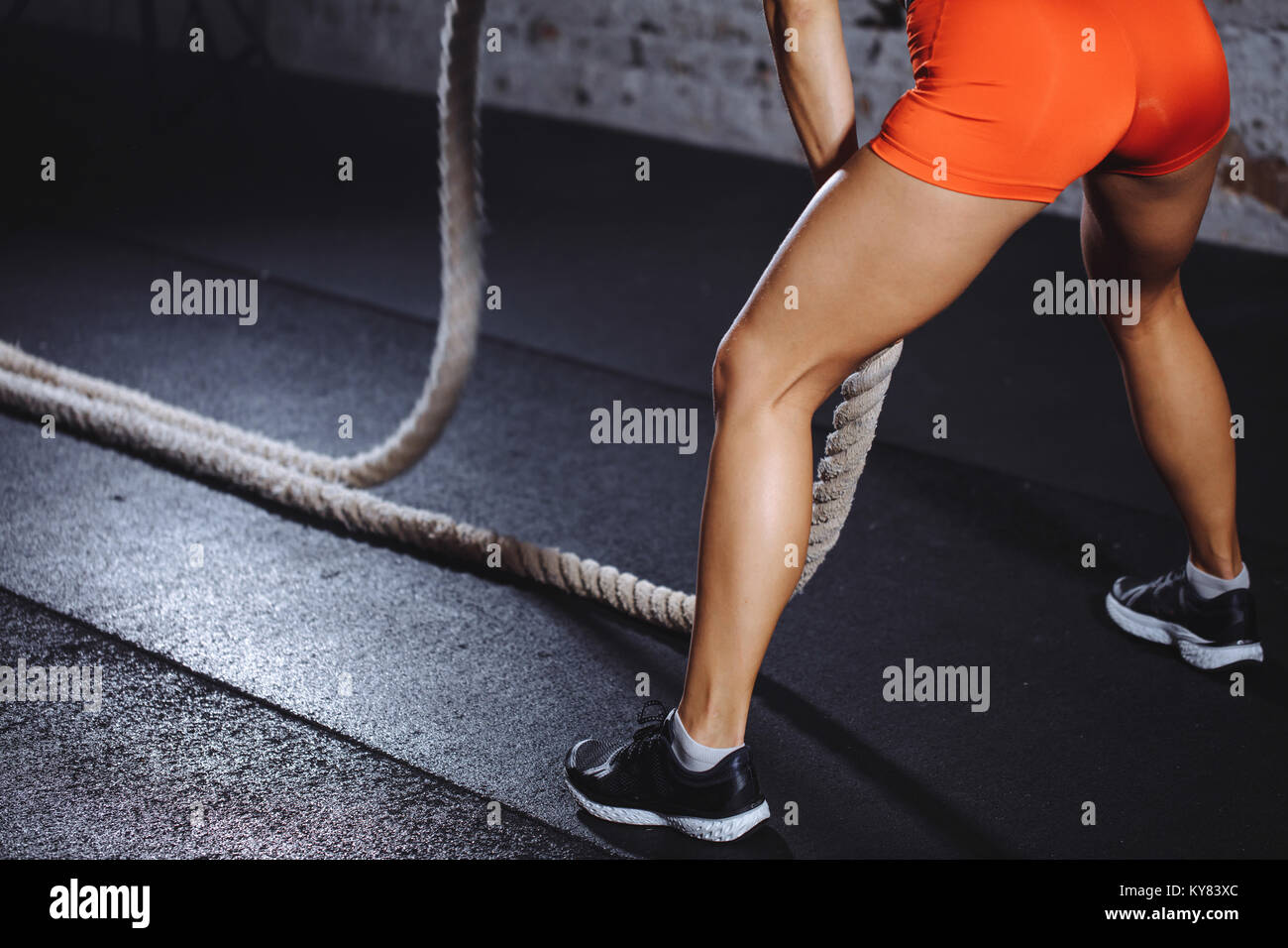 rear view of tonned woman training with battle rope in cross fit gym - Stock Image