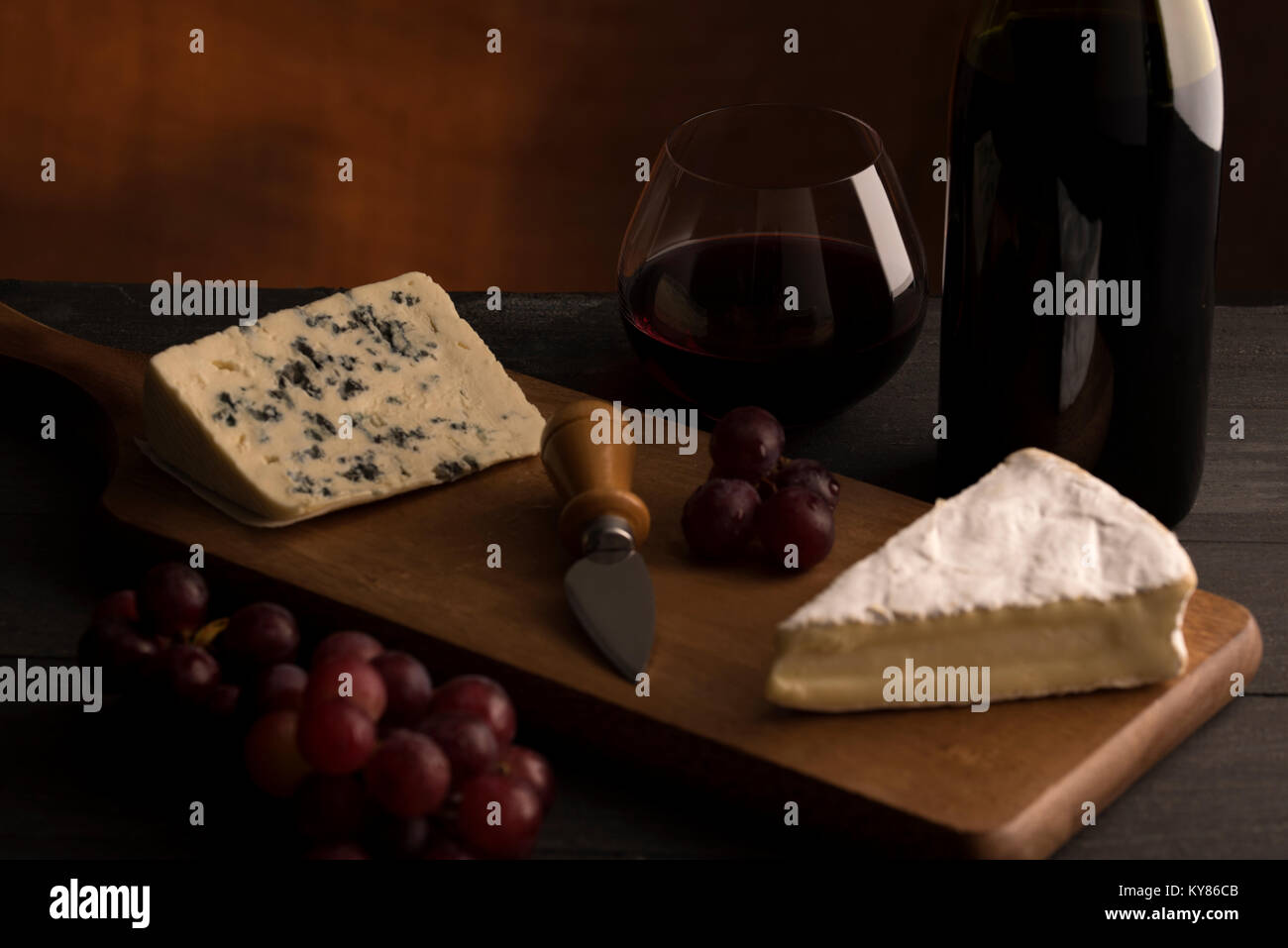 Red wine in stemless glass with wine bottle red grapes  and cheese - Stock Image