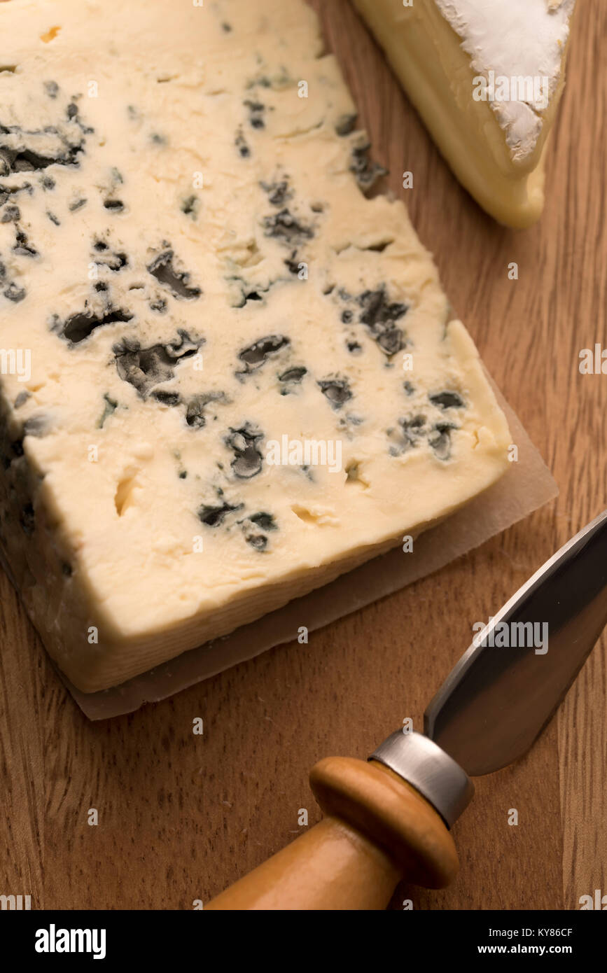 Blue cheese, camembert with cheese knife on wooden background - Stock Image