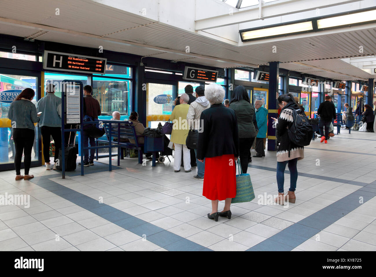 Passengers waiting for buses in North Road bus station, Durham, England - Stock Image