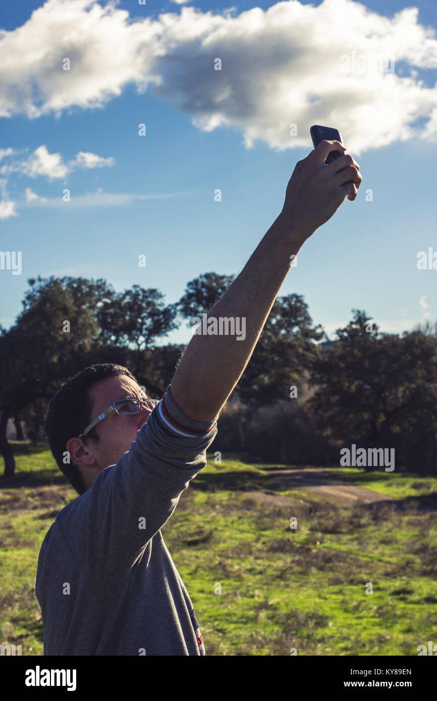 Boy looking for mobile coverage in the mountain - Stock Image