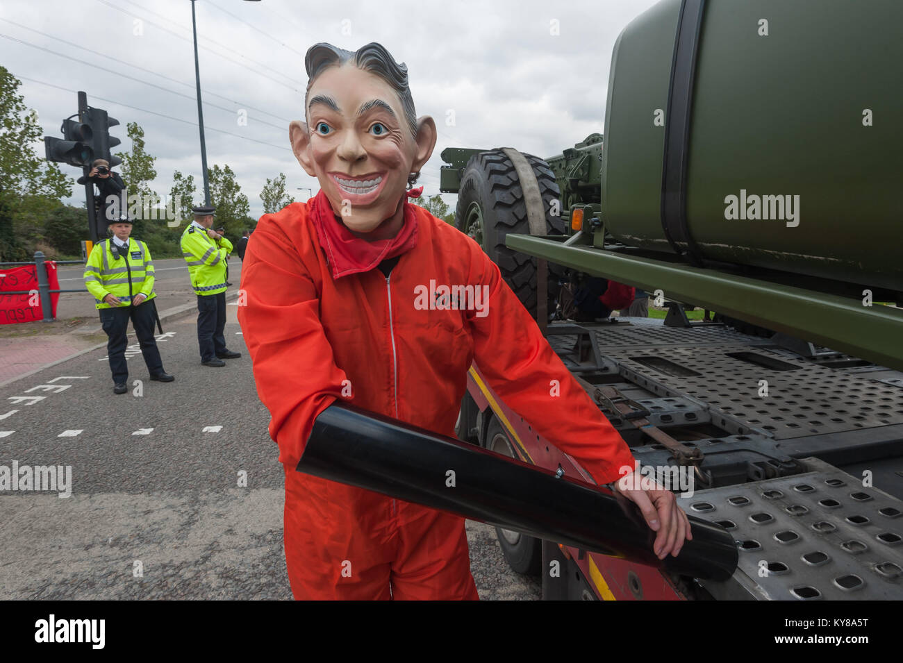 Occupy Democracy protester 'Tarpaulin Simon' wearing a Blair mask is locked on to the lorry stopped at 'Stop Arming Stock Photo
