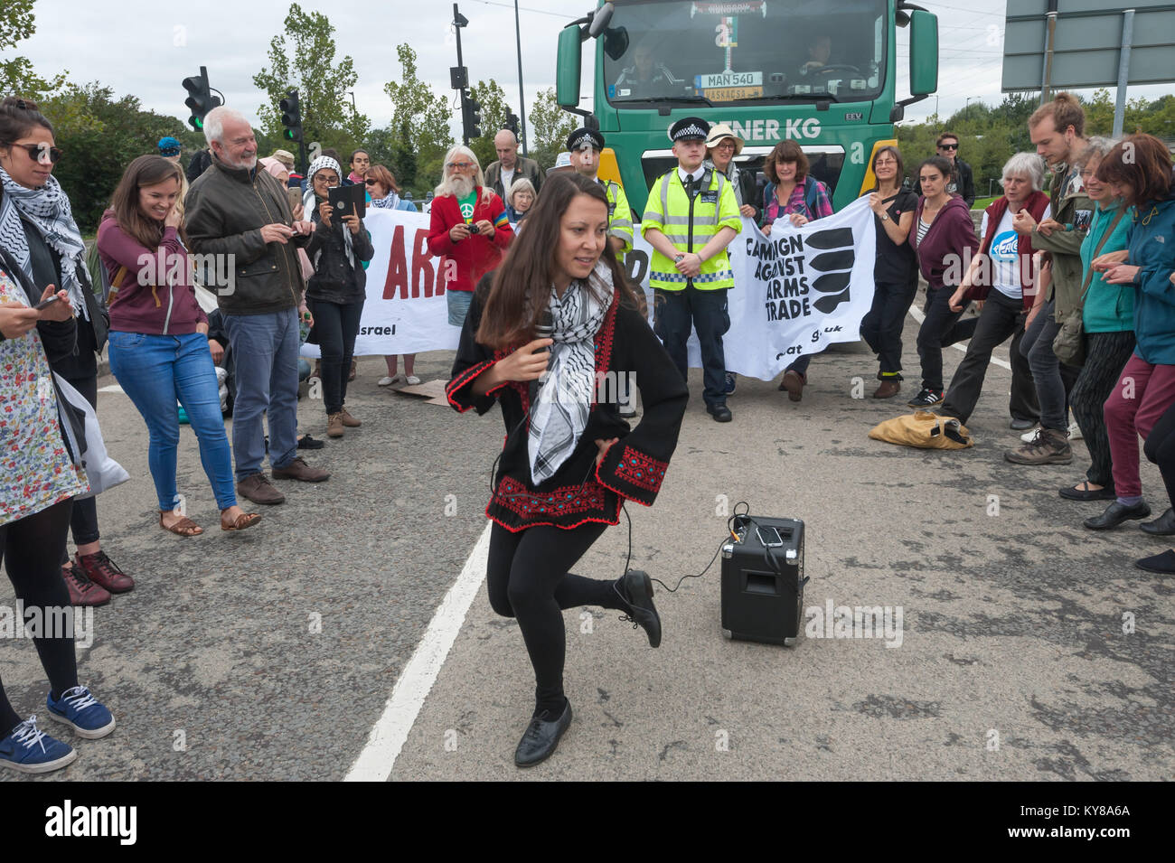 A woman leads a Dabke Dance workshop on the road in front to the stopped loryy at 'Stop Arming Israel', the first Stock Photo