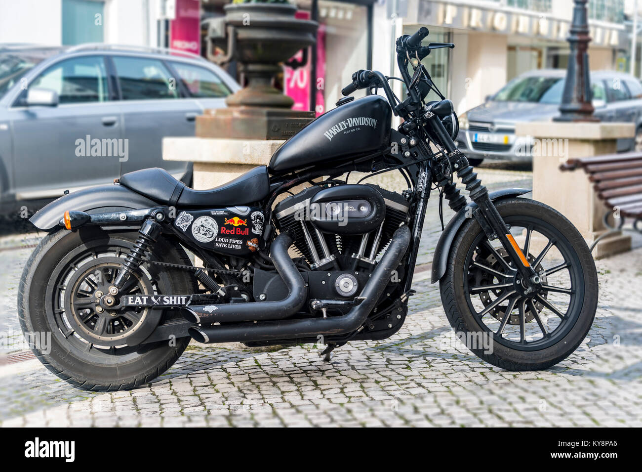 Harley Davidson motorcycle in matte black parked on a cobbled street in Portugal. - Stock Image