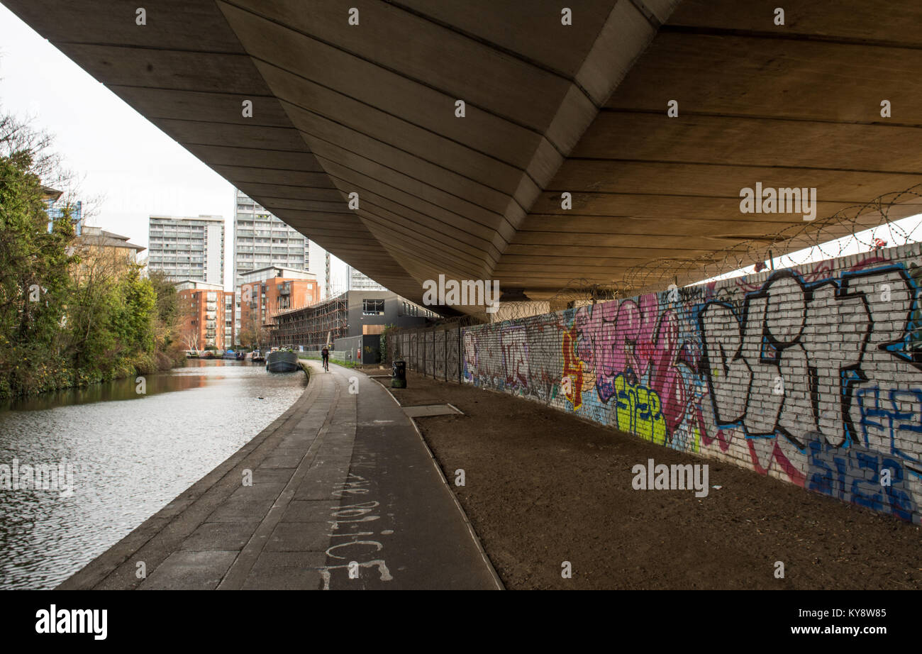 London, England, UK - December 19, 2015: The Westway motorway runs above the graffiti-strewn Grand Union Canal towpath - Stock Image
