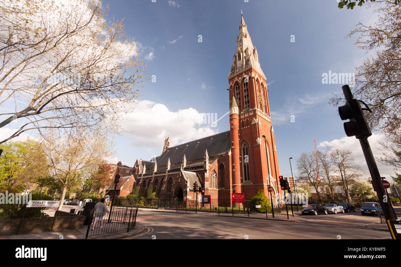 London, England, UK - April 12, 2011: Sun shines on the red brick Victorian Gothic tower and spire of St John the - Stock Image