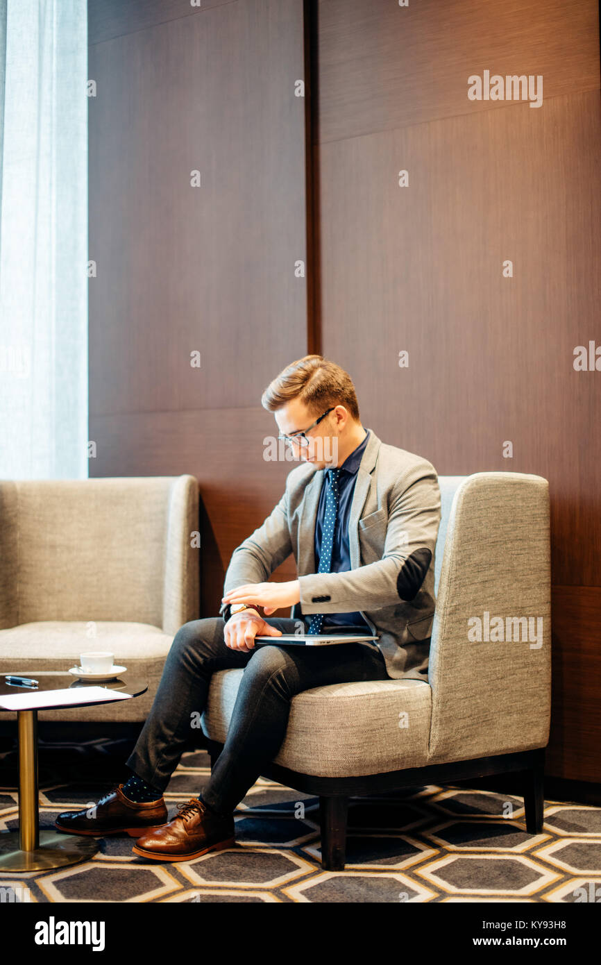 man is preparing for interview. He in suit, sitting in hall on chair, waiting - Stock Image