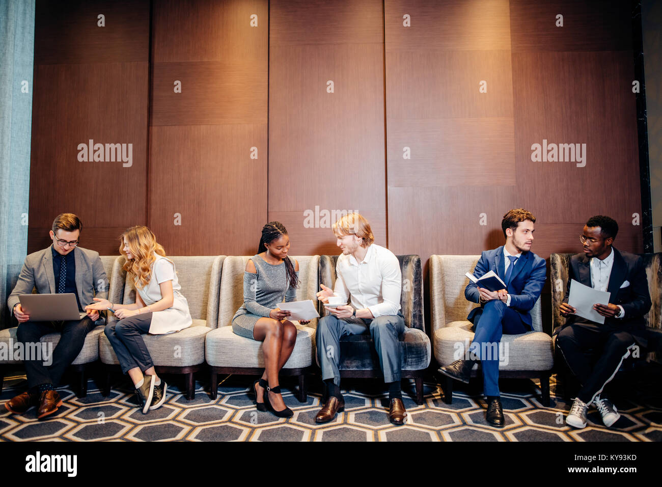Business people waiting for job interview, talking - Stock Image