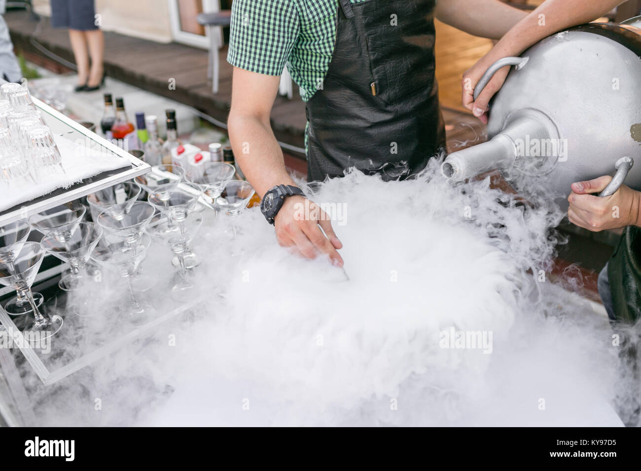 bartenders serve the cocktail in a large bowl with liquid nitrogen. row line of different alcoholic cocktails on - Stock Image