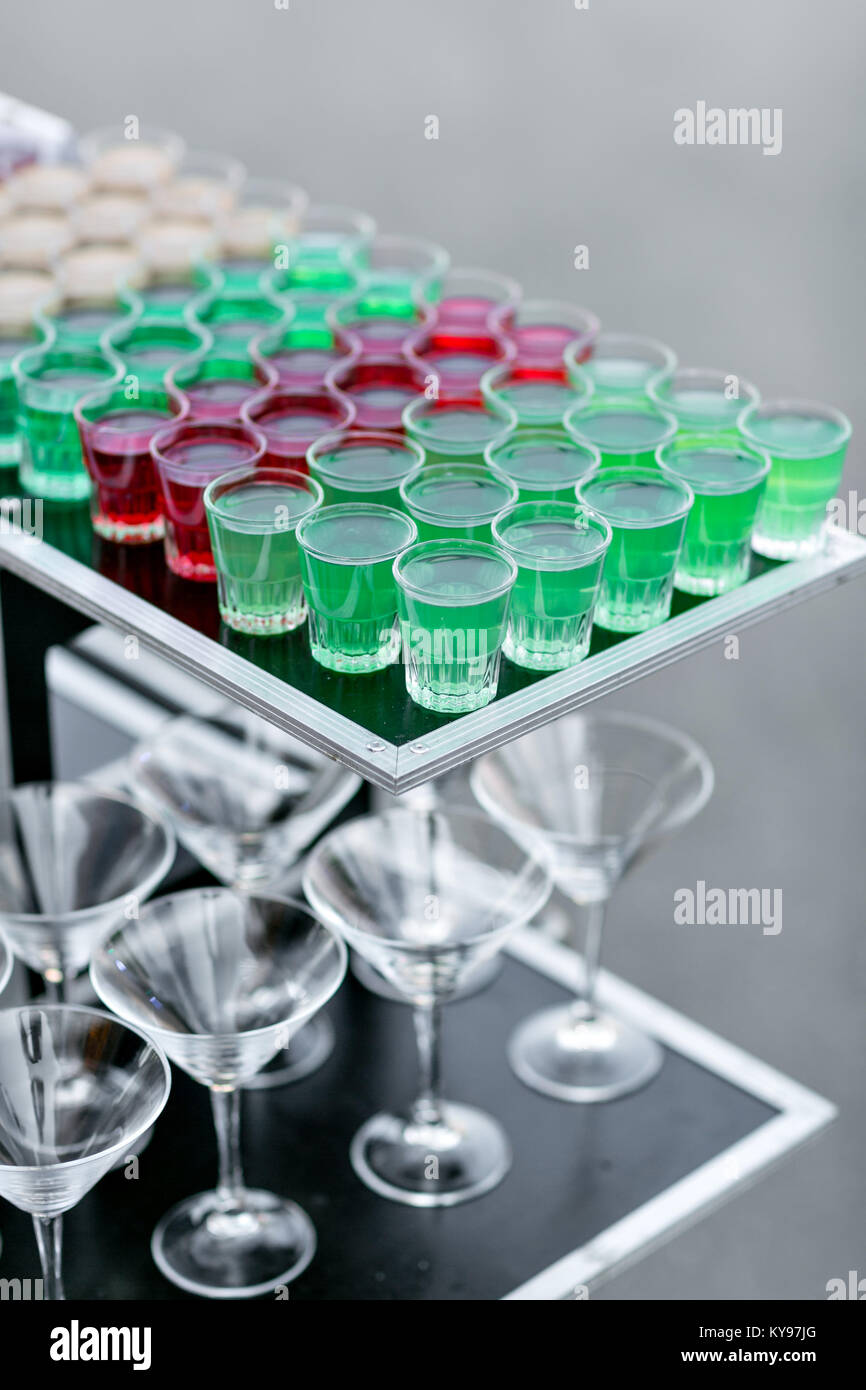 row line of different colored alcoholic cocktails on a party. wedding day or birthday - Stock Image